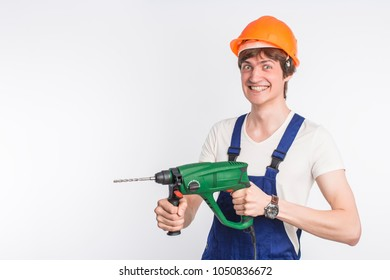 young guy in overalls and orange helmet holds puncher on white background.