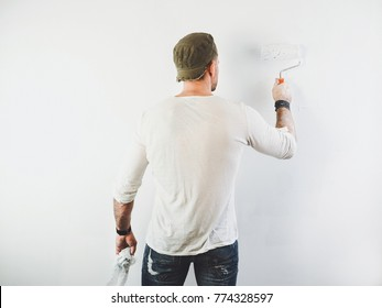 young guy painting a wall in the house with a paint roller