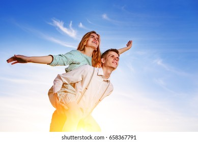 Young guy piggybacking cheerful girlfriend like airplane on the background of sky.