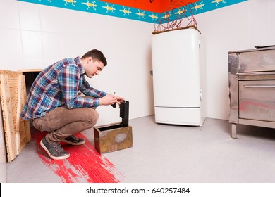 Young guy in plaid shirt squatting and opening the safe trying to get out of the kitchen with a bloody floor, escape the room game concept