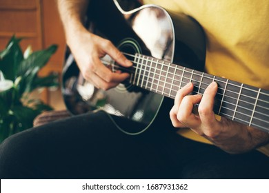 A young guy is playing a guitar at home, trying to break through stressful barriers and just get lost in some music. Selective focus and natural light, beautiful bokeh.