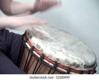 A young guy is playing on his Djembe