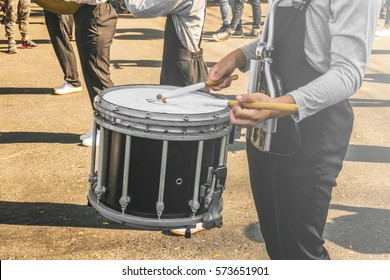 A young guy is playing snare during parade show in a sunny day.