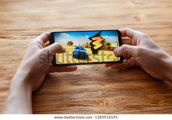 Young Guy Plays Asphalt 9 Mobile Stock Photo (Edit Now