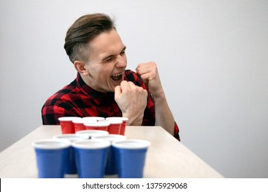 a young guy plays beer pong, he won and is happy