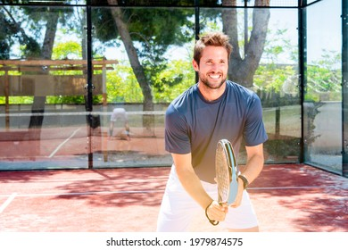 young guy plays padel tennis outdoor summer sport court getting fit