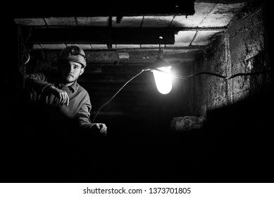A young guy in a protective suit and helmet sits in a tunnel with a burning scrapbook. Miner in mine