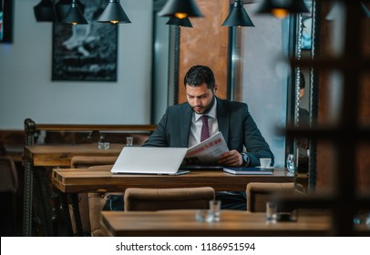 a young guy in the reading room reading a morning newspaper in a cafe