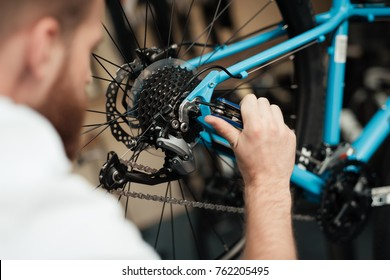 A young guy repairs a bicycle. He's wearing an apron. He works in the workshop.