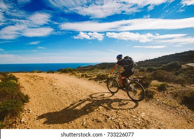a young guy riding a mountain bike on a bicycle route in Spain on a dirt road against the background of the Mediterranean Sea. Dressed in a helmet, a dark one and a black backpack