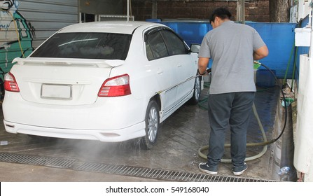 Young guy rinsing the soap of the car wheel by stream of water