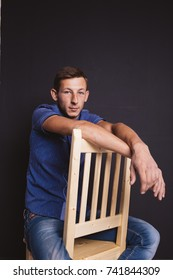 young guy with a scar on his nose posing in a photo Studio. business style in clothes: shirt and jeans. emotional portrait. short hair and clean skin
