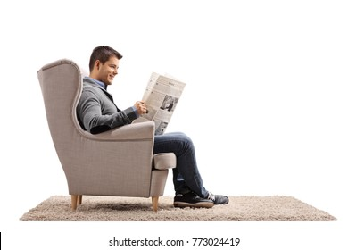 Young guy seated in an armchair reading a newspaper isolated on white background