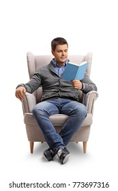 Young guy seated in an armchair reading a book isolated on white background
