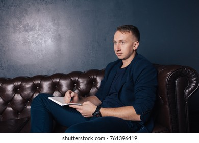 young guy in the shirt. emotional portrait. short hair and clean skin. makes notes in his notebook. sitting on a leather sofa