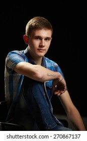 young guy in a shirt, a photo shoot in a studio on a dark background