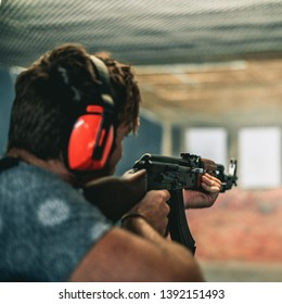 Young guy shooting an AK47 in a shooting range with ear protection on
