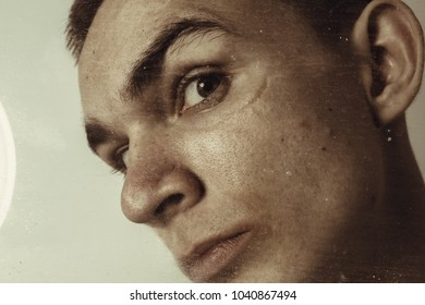 young guy with short hair and big ears. emotional portrait of a student close-up through a dirty window frame. psychological diseases: depression and madness