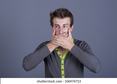 Young guy shut your mouth on a gray background in the studio