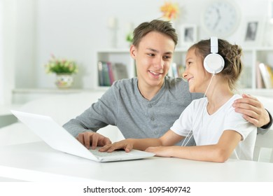 young guy with sister sitting at table with laptop and listen to music
