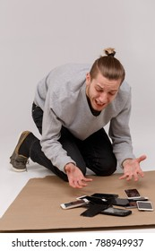 A young guy sits on the floor and cries over a bunch of broken smartphones.