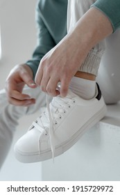 young guy sits and ties the laces on white sneakers
