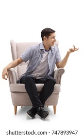 Young guy sitting in an armchair and talking isolated on white background