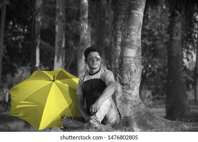 Young guy sitting beside a yellow umbrella