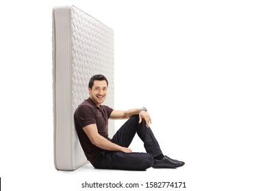 Young guy sitting on the floor and leaning against a bed mattress isolated on white background
