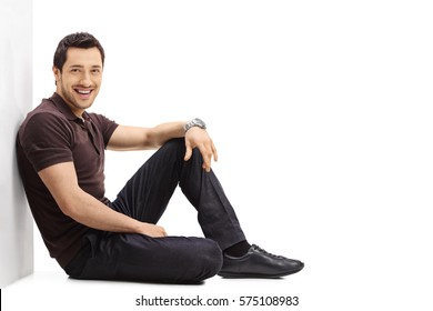 Young guy sitting on the floor and leaning against a wall isolated on white background