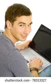 A young guy sitting on the floor with a laptop, back-view