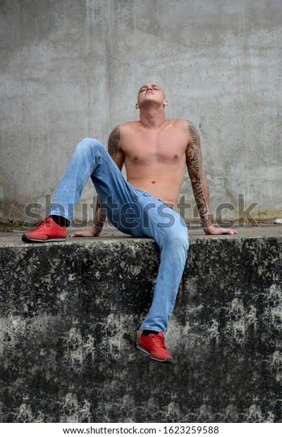 Young guy sitting outdoor on wall with his head raised.