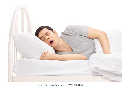 Young guy sleeping on a bed covered with a white blanket isolated on white background