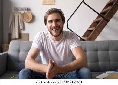 Young guy speaking recording vlog at home looking at camera, male vlogger talking shooting video blog webinar