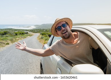 Young guy with straw hat leaning out of side window from his car while enjoying car travel during holiday vacation. Man chilling sunny day in countryside and the beautiful nature landscape in afrika.