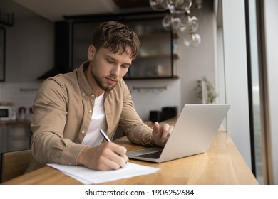 Young guy student prepare research essay at modern kitchen surf internet use laptop write up information to paper report by hand. Focused man freelancer work from home make list of data from pc screen - Shutterstock ID 1906252684