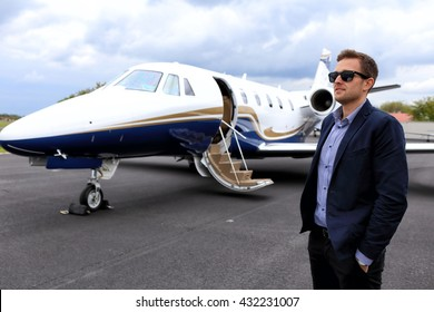 Young guy with sunglasses in front of executive jet with open doors