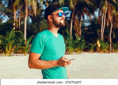 young guy in sunglasses t-shirt talking on the smartphone to respond to messages texting,I love selfie! holding camera smiling while standing against grey background outdoor portrait, close up,bearder