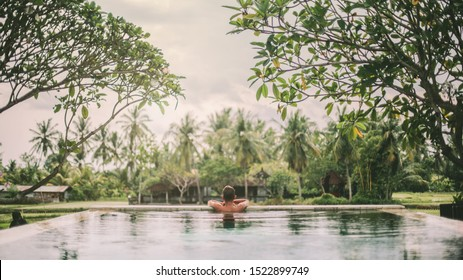 Young guy swimming in infinity pool with a view on rice terrace. Travelling to Ubud, Bali.