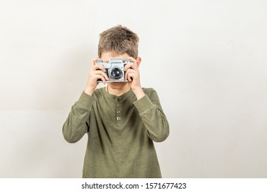 young guy takes pictures with a film camera