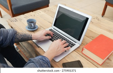 young guy with tattoed arm using a laptop