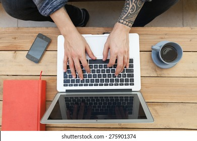 young guy with tattooed arm using a laptop