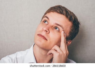 young guy thinks his finger to his temple