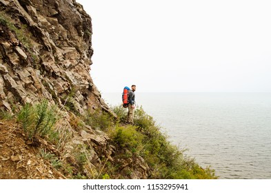 Young guy tourist with backpack on lake and mountains background