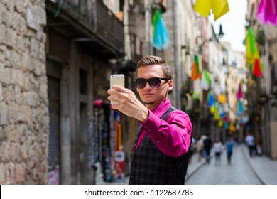 A young guy, a tourist does selfie on a mobile phone in the street Girona, decorated with colorful shawls, a trip to Spain