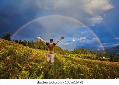 a young guy, a tourist, raised his open palms and raised his hands and face upwards, rejoicing in the rainbow