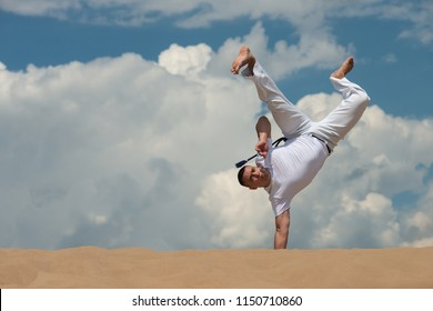 A young guy trains capoeira against the sky. The concept of people, lifestyle and sports. A man performs an acrobatic trick