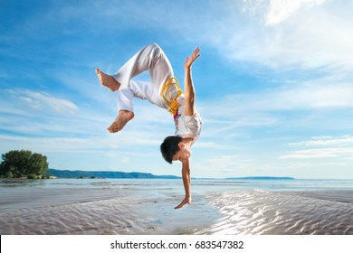 A young guy trains capoeira on the beach - concept about people, lifestyle and sport.