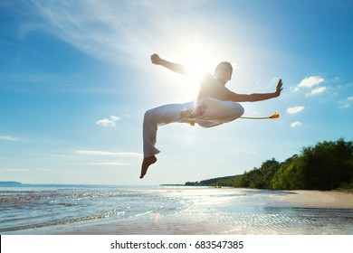 A young guy trains capoeira on the beach.  - concept about people, lifestyle and sport. A boy performs martial the kick in the jump. The silhouette against the sunlight