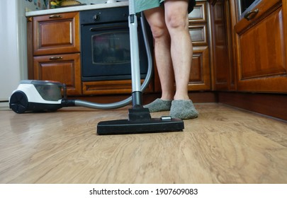A young guy uses a vacuum cleaner while cleaning the plot of the house in the kitchen